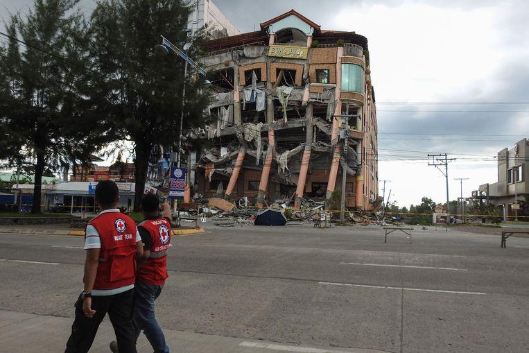 Hulpverleners wandelen langs een beschadigd gebouw.