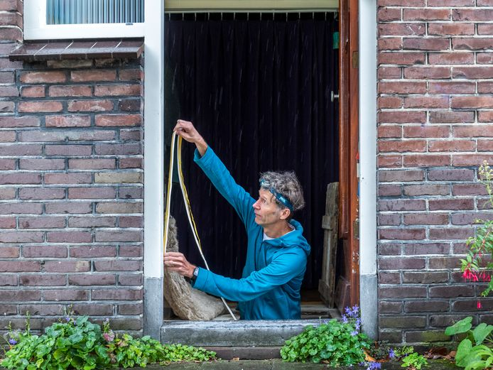Energie ambassadeur Harry Boerma brengt tochtstrips aan.