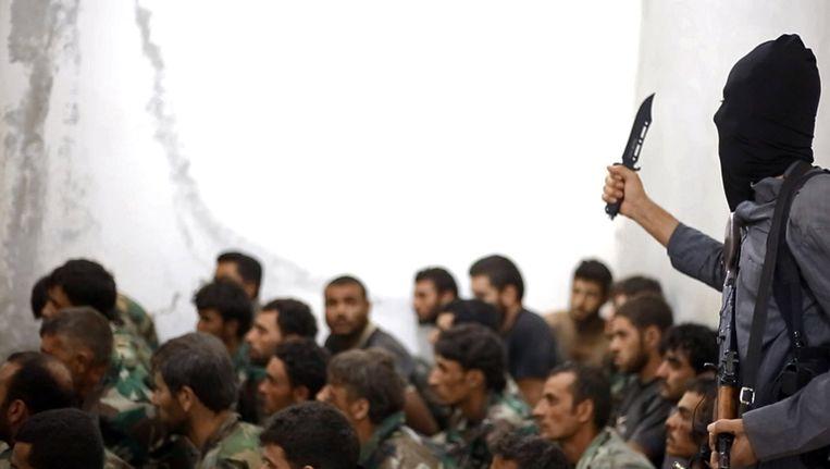 Een IS-strijder bewaakt Syrische soldaten bij Raqqa. Beeld ap