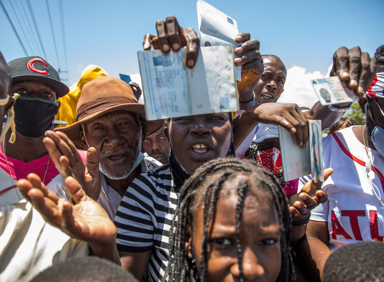 Haïtianen zwaaien met paspoorten bij de Amerikaanse ambassade om een visum te krijgen