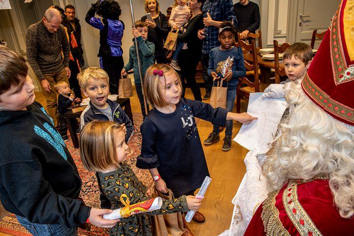 De kinderen geven hun tekeningen aan de Sint.