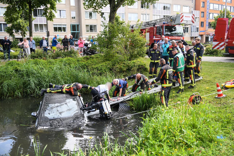 De vrouw wordt uit de auto gehaald door de brandweer.