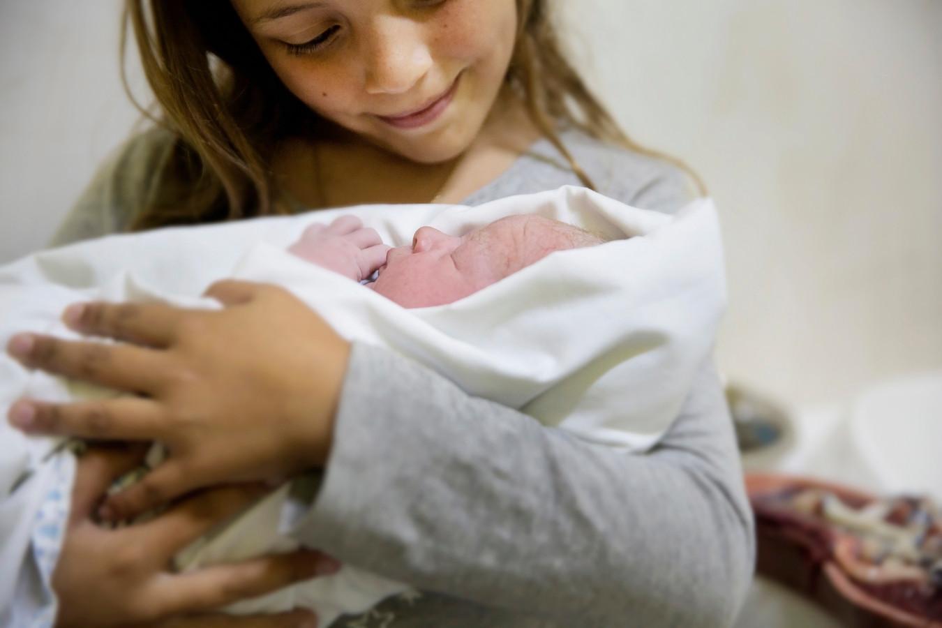 Een trotse zus houdt haar pasgeboren broertje vast.