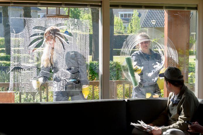 Ontwerper Manon van Hoeckel (links) en haar stagiaire Casey Voogd wassen de ramen bij een woonhuis van Severinus Severinus terwijl bewoners toekijken.