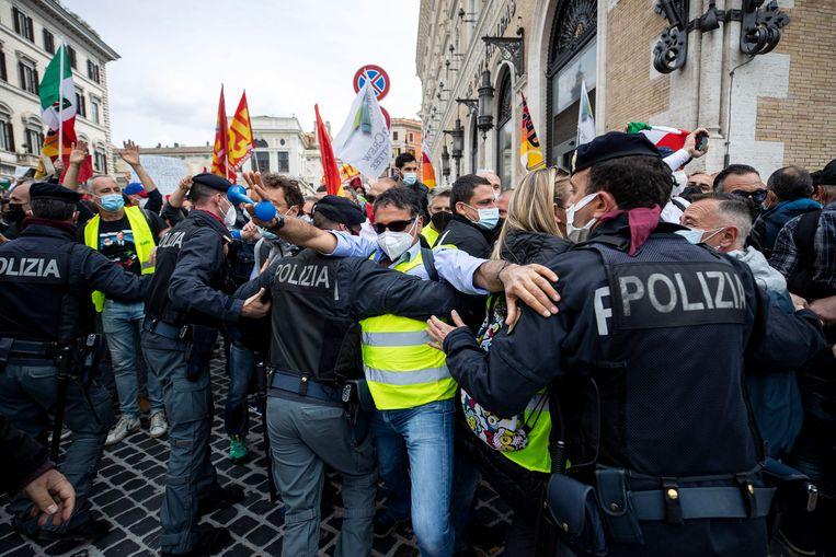 De Italiaanse politie, die hier demonstranten in bedwang probeert te houden, houdt tegenwoordig regelmatig undercover-acties om te controleren of ambtenaren zich aan hun werktijden houden.  Beeld EPA
