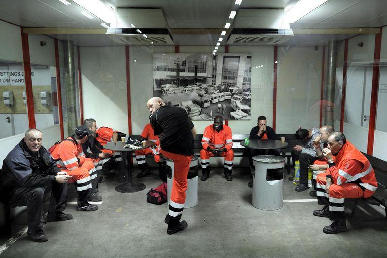 Amsterdamse vuilnismannen en straatvegers doen een pafje in de rookruimte. Beeld Joost van den Broek