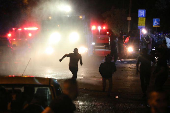 Palestijnse demonstranten rennen weg nadat de Israëlische politie waterkanonnen op hen inzet. Beeld van eerder deze maand in Oost-Jeruzalem.