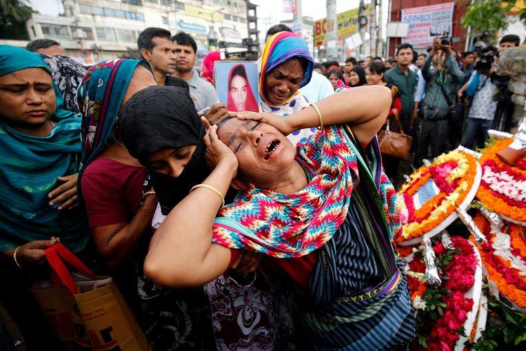 Een vrouw huilt bij een herdenking van het Rana Plaza-drama. Beeld REUTERS