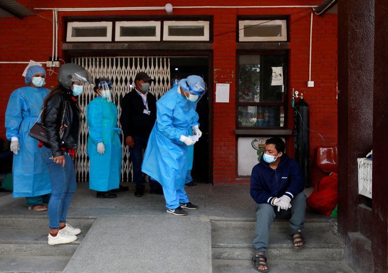 Een besmette man wacht op hulp voor de ingang van een ziekenhuis in Kathmandu. Beeld REUTERS