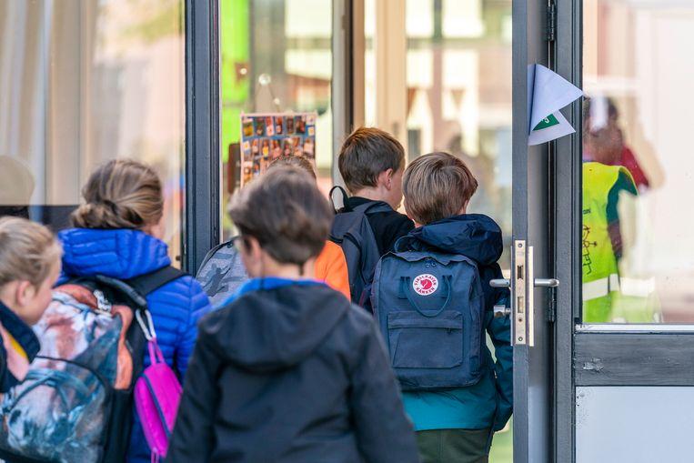 Via schoolkinderen komt het virus vaak de gezinnen binnen, menen experts in Nederland, Duitsland en zowat elke grote Amerikaanse stad. Waarom denken ze daar hier anders over? Beeld Photo News