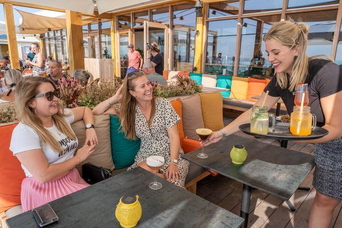 Bedrijfsleider Michelle van Sliedrecht van strandpaviljoen Bombaai brengt Joelle van Hal (l) en Romy Lamper (m) frisse cocktails.