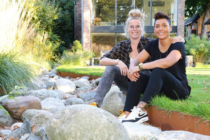 Femke van Veen (links) en Annette Soleman in hun tuin. Het koppel is vanavond op tv te zien in het programma Wie heeft de mooiste bruiloft?
