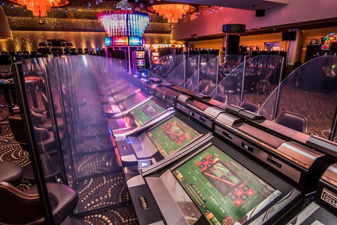Spatschermen tussen de speeltafels bij Holland Casino in Enschede.