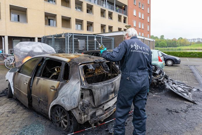 Een medewerker van Forensische Opsporing is bezig met sporenonderzoek bij de afgebrande auto in de Staatssecretarislaan in Zwolle.