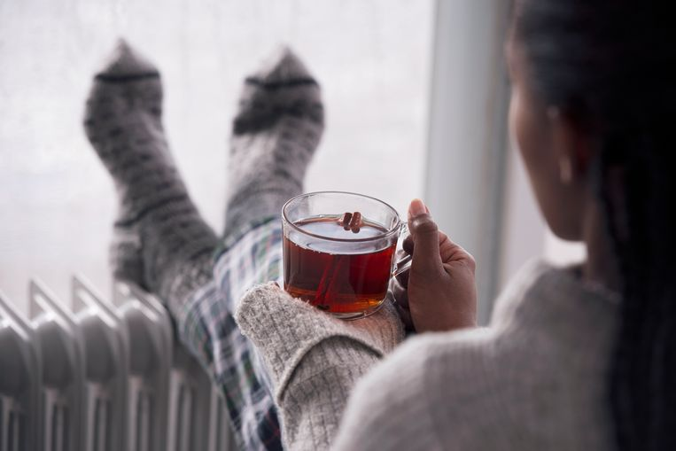 Over the shoulder view of a woman drinking hot tea, heating feet on the radiator heater, wearing woolen socks, sitting next to a window, staying at home in the rainy winter season. Selective focus on the cup of tea. Beeld Getty Images