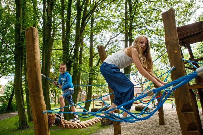 Een jongen en een meisje testen het klimparcours uit.