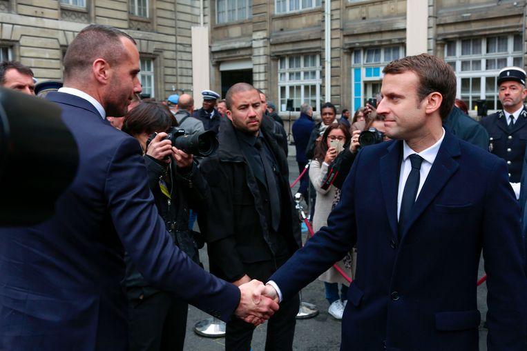 Presidentskandidaat Emmanuel Macron was ook aanwezig en schudt Jugelé's vriend, Etienne Cardiles, hier de hand. Beeld AFP