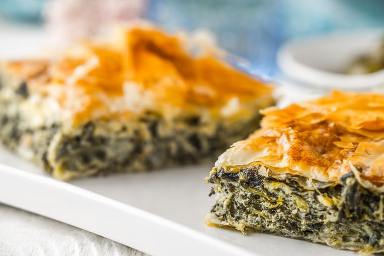 Greek pie spanakopita on the white plate on the white wooden table with  blurred accessorizes horizontal Beeld Getty Images/iStockphoto
