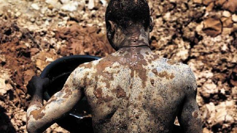 Een goudzoeker in Mozambique graaft zonder beschermende kleding in de modder, die vol zit met chemicaliën. (Trouw) Beeld