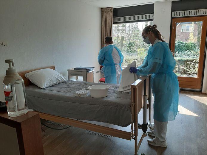 Personeelsleden in het noodhospitaal De Dillenburg in Ermelo maken de ziekenhuisbedden op.