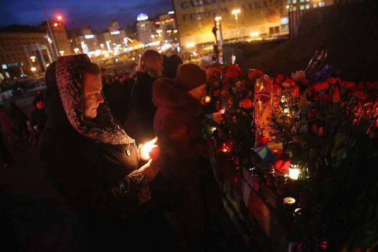 Mensen branden kaarsen en leggen bloemen op het Maidanplein in Kiev. Beeld getty