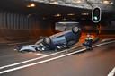 Een agent maakt foto's van het wrak van een over de kop geslagen auto in de Willemstunnel in Arnhem. Het ongeluk gebeurde in mei van dit jaar.