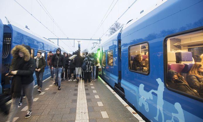 Dringen voor de trein op het perron in Raalte.