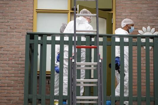 Onderzoek door mannen en vrouwen in witte pakken in en rond de woning.