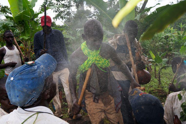 Een jongen danst met houten stokken voorafgaand aan zijn besnijdenis terwijl dorpelingen hem bespugen met een lokaal brouwsel. Beeld Michele Sibiloni