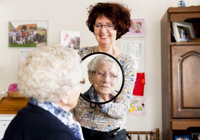 Kapster Dolly brengt het haar van een bewoonster van verzorgingshuis in Didam in model. Beeld anp