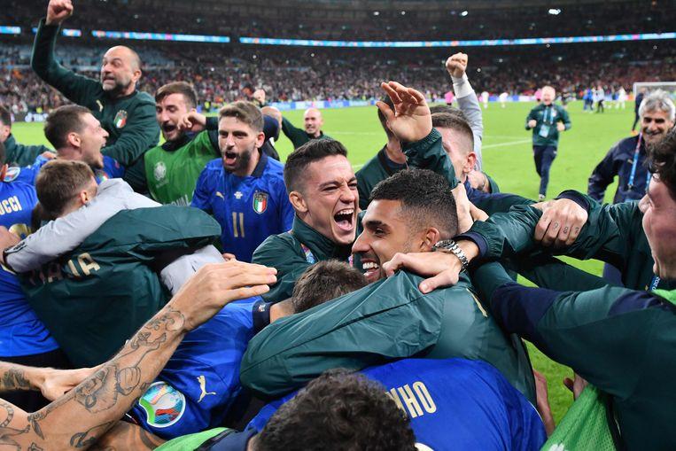 Italië staat in de finale van het EK na de beslissende strafschop van Jorginho, die op de voorgrond bijna wordt bedolven onder teamgenoten. Beeld AFP