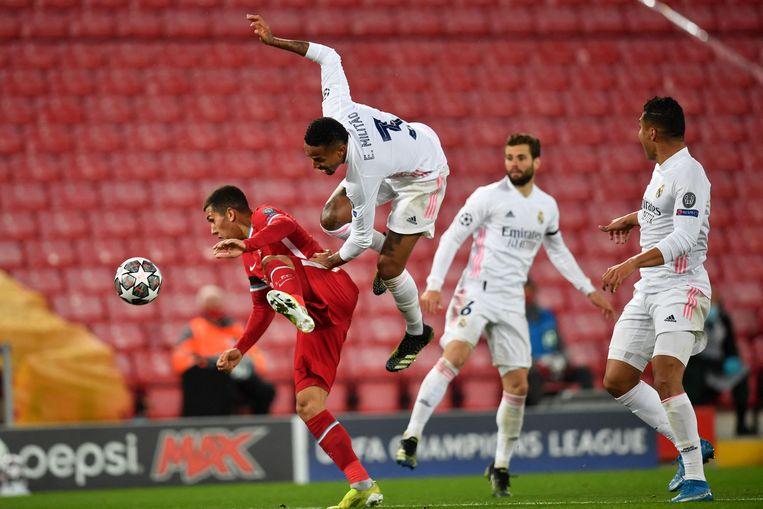 Liverpool-aanvaller Roberto Firmino (l.) krijgt een vliegende Eder Militão van Real Madrid in de rug, tijdens hun Champions League-kwartfinale in april. Beide clubs zouden deel uitmaken van de Super League. Beeld AFP