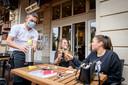 Ook net over de grens, in Gronau, zijn de terrassen weer open. Daar loopt het personeel met een mondkapje op. Matthias van Extrablatt brengt een fles wijn aan Pascalle Monnink (R) en Tamara Voorhuis uit Enschede.