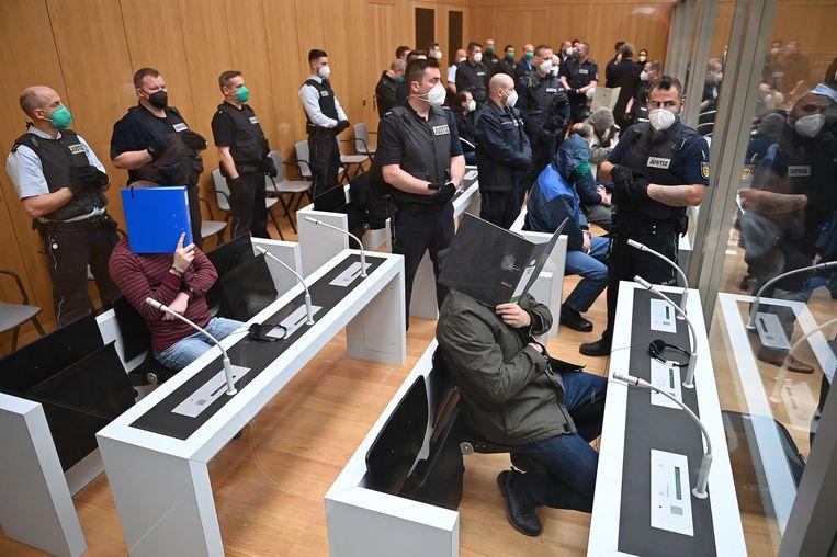 In een rechtbank in Stuttgart houden verdachten hun gezicht verborgen voor de fotograaf. Beeld EPA