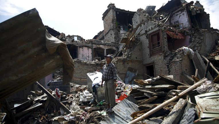 Een man tussen het puin van zijn huis in Sankhu. Enkele weken na de vorige aardbeving sloegen de onderaardse krachten in de regio weer dodelijk toe. Beeld REUTERS