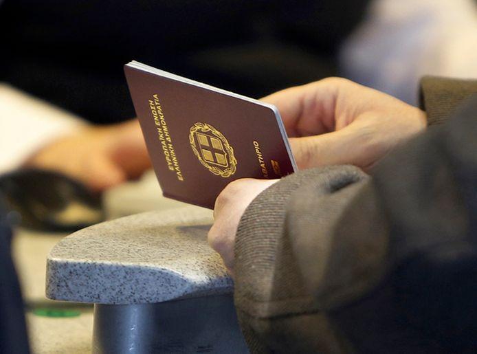 Een reiziger toont zijn Griekse paspoort bij een douanecontrole