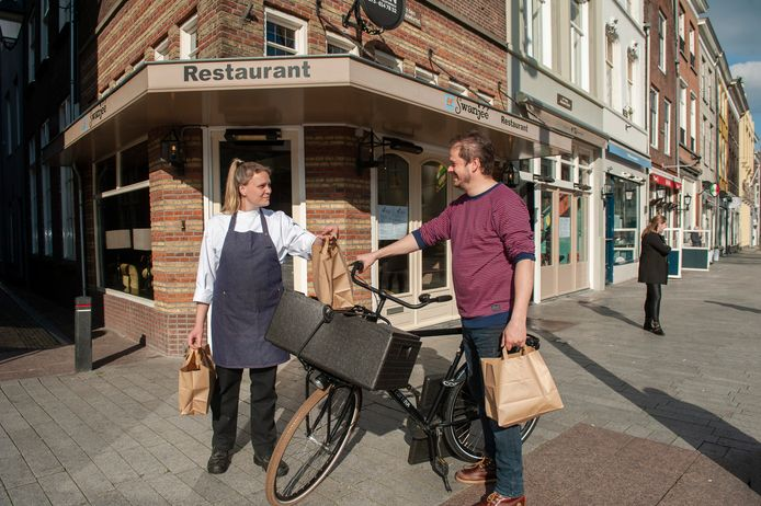 Jessica van Esdonk, kok bij Restaurant ff Swanjéé in de Hinthamerstraat overhandigt bestelde maaltijden aan bedieningsmedewerker Wouter Rip