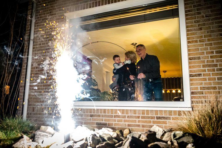 Een familie in Geldrop steekt vuurwerk af tijdens oudejaarsavond op anderhalve meter afstand.  Beeld ANP