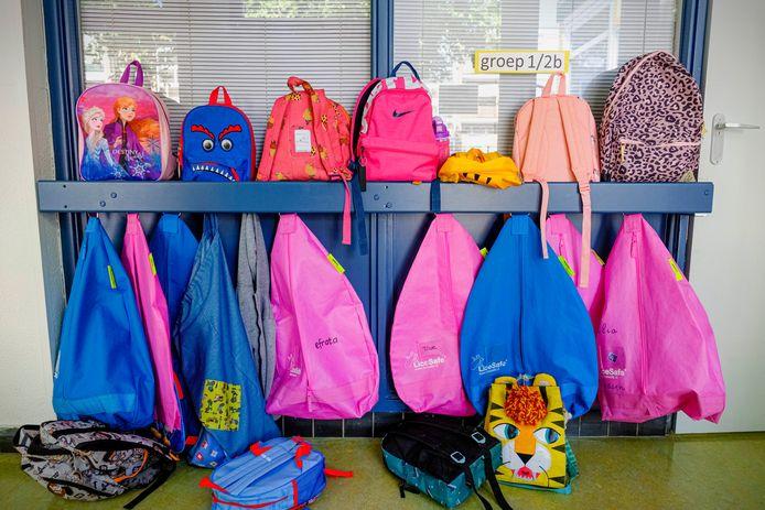 Tassen van groep 1/2 aan de kapstok op de basisschool.