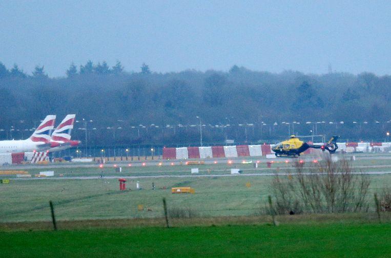 Een helicopter in de buurt van de landingsbaan op Gatwick Airport. Beeld AP