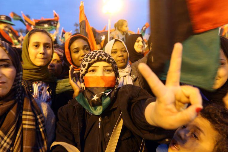 Libische vrouwen nemen op straat deel aan de festiviteiten en flashen het vredesteken. Beeld AFP