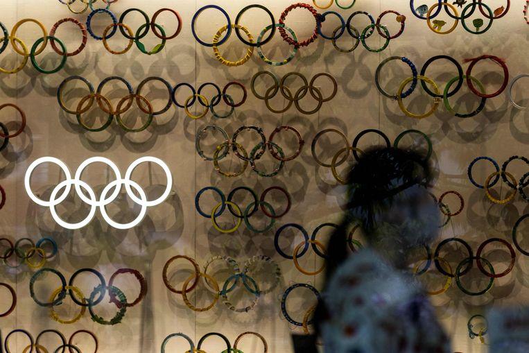 Een medewerker van het Japans olympisch museum loopt langs een wand met de olympische ringen. Beeld AFP