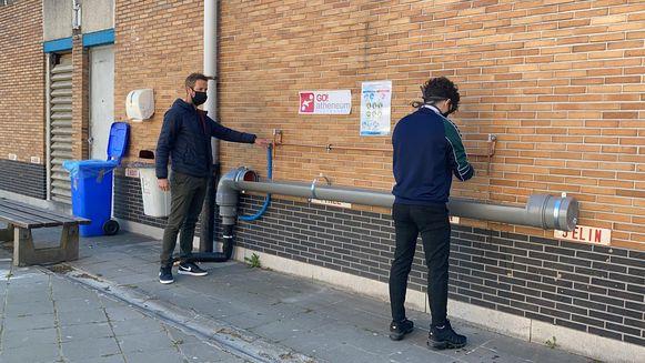 Handen wassen en ontsmetten doen de leerlingen aan een installatie die is opgehangen aan een buitengevel.