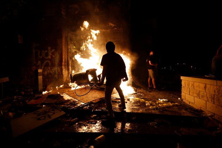 Demonstranten wakkeren het vuur aan dat woedt in het politiebureau van Minneapolis. Beeld AP