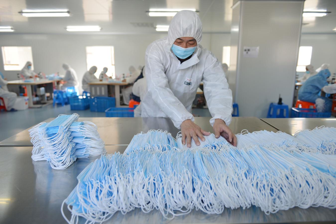 Een werknemer sorteert gezichtsmaskers in een fabriek in China.