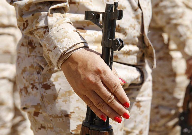Een vrouw houdt de hals van een geweer vast. Beeld reuters