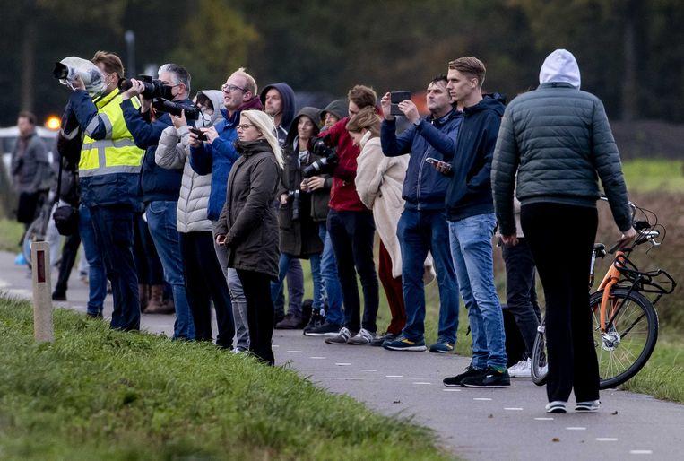 Vliegtuigspotters zien een Boeing 747-400 van KLM voor de laatste keer op Schiphol landen. Beeld ANP