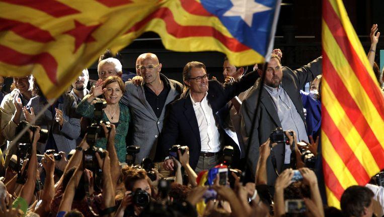 De leiders van onafhankelijkheidslijst Junts pel Sí aan het feest: Artur Mas (m.) wordt geflankeerd door Raül Romeva (l.) en Oriol Junqueras. Beeld © epa
