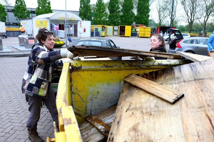 Deze dames steken de handen uit de mouwen en gooien sloophout in de container.