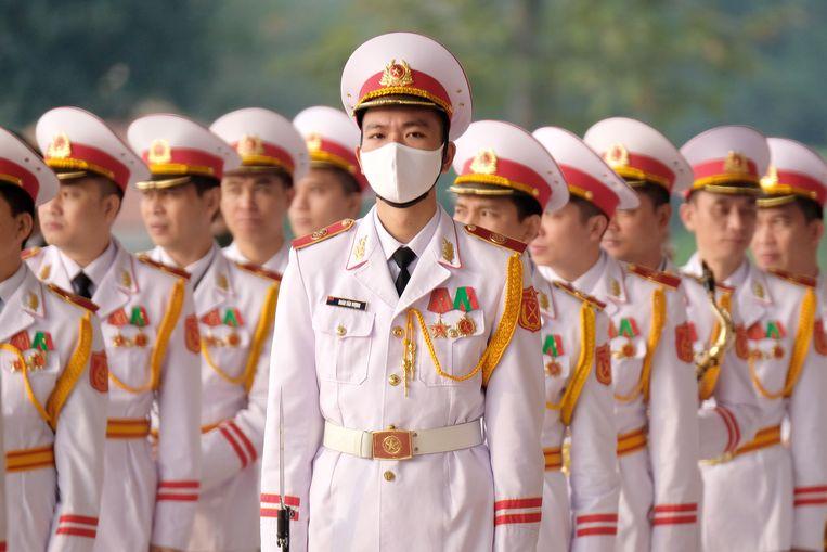 Bij de erewacht in de stad Hanoi droeg gisteren niet iedereen een mondkapje. Vietnam wordt geprezen om zijn succesvolle aanpak van het virus, met 1850 besmettingen en 35 doden. Uit vrees voor de Britse variant zo net voor Nieuwjaar gingen gisteren scholen vroeg dicht en moest ook deze erewacht bij het Communistisch Congres eerder naar huis.  Beeld EPA